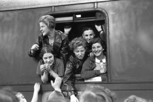 Schwarzweiß Aufnahmen von fünf Jugendlichen, die aus den Fenster eines Zugabteils winken