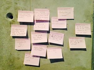 Nahaufnahme einer grauen Wand mit beschrifteten rosa Notizzetteln