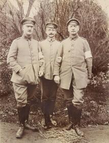 schwarz-weiß Fotogfrafie mit drei uniformierte Sodaten frontal und stehend vor einer Grünanlage