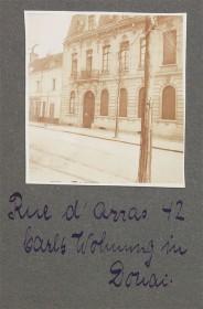 schwarz-weiß Fotografie eines Hauses mit Straßenausschnitt, eingeklebt in einem Fotoalbum mit Bildunterschrift