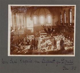 schwarz-weiß Fotografie eines Krankensaals mit mehreren Personen eingerichtet in einer Kirchenkapelle