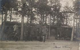 schwarz-weiß Fotografie mit mehreren uniformierten Soldaten zum Teil sitzend und stehend vor einer Hütte im Wald