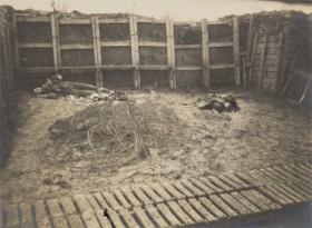 schwarz-weiß Fotografie mit Blick in einen Schützengraben mit einem totem Soldaten liegend