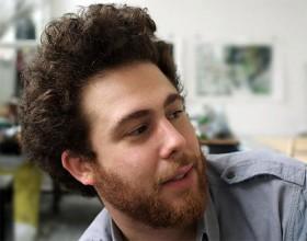 Portätfotografie eines jungen Mannes mit Bart und lockigem Haar, nach rechts blickend