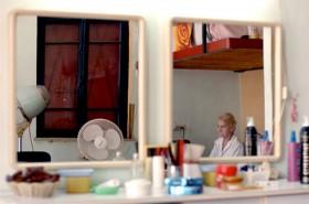 Farbfotografie mit zwei Spiegeln an einer Wand und Spiegelung einer sitzenden alten Frau