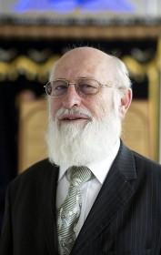 Älterer Herr im Anzug mit Brille und Vollbart