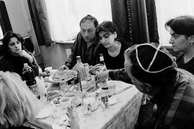 Eine Familie sitzt um einen reichlich gedeckten Tisch und isst