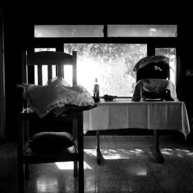 Schwarz-weiß Fotografie zeigt einen Tisch vor einem Fenster mit einer Babyschale, links davon ein Stuhl