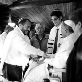 Schwarz-weiß Fotografie zeigt mehrere Menschen, die um einen Mann herumstehen, der ein Baby auf dem Schoß hat