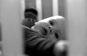 Schwarz-weiß Fotografie mit einem Kleinkind in einem Gitterbett