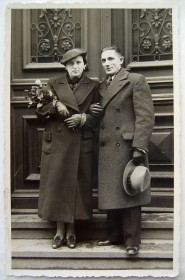 Schwarz-Weiß-Fotografie eines Paares auf einer Treppe, sie hat einen Blumenstrauß in der Hand