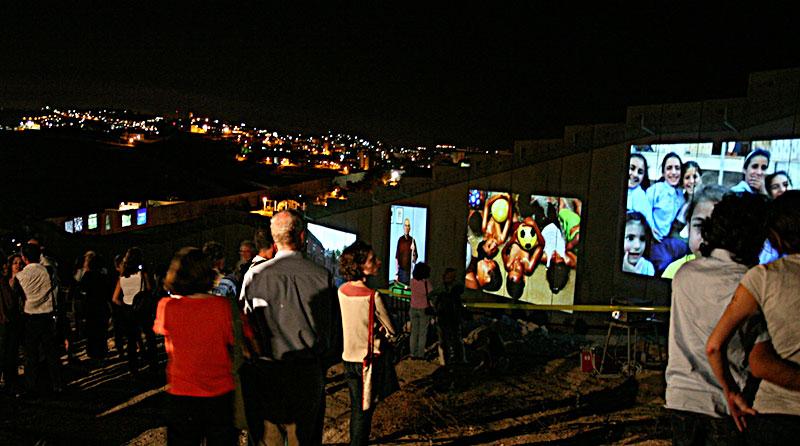 Farbfotografie einer Kunstinstallation mit Bildprojektionen an eine Mauer im Dunkel mit Menschen davor und einem Weitblick auf dahinter liegende beleuchtete Wohnhäuser