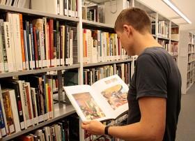 Ein Mann mit einem Buch in der Hand vor Bücherregalen