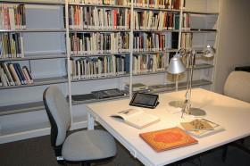 Tisch mit Büchern und Tablet, im Hintergrund Bücherregale