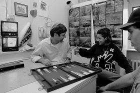 Schwarz-weiß Fotografie: Ein Mann und zwei Jugendliche spielen Backgammon