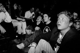 Schwarz-weiß Foto: Jugendliche sitzen auf dem Boden und auf Stühlen