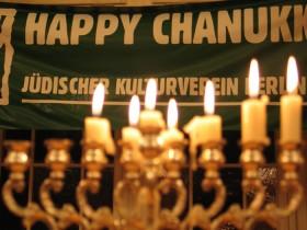 """Chanukkaleuchter mit brennenden Kerzen, dahinter ein Banner mit der Aufschrift """"Happy Chanukka. Jüdischer Kulturverein Berlin"""""""