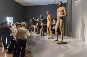 Viele Meschen stehen vor einer erhöhten Plattform auf der verschiedene nackte männliche Statuen stehen