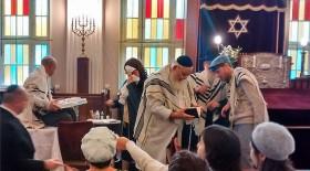 Farbfotografie einer Beschneidungsfeier in der Synagoge mit mehreren Personen