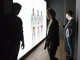 Junge Menschen stehen vor einer hell erleuchteten Wand auf der drei gleichaussehende nackte Männer zu sehen sind, vor deren Penissen Länderkarten von Deutschland, Israel und der Türkei zu sehen sind