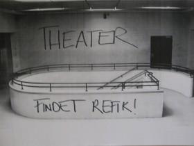 """Ein graues Treppenhaus an dessen Wand der Satz """"Theater. Findet Refik"""" angesprüht ist"""