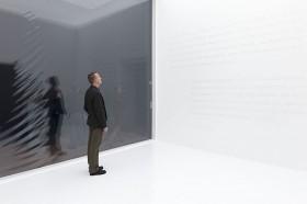 Ein Mann steht in einem weißem Raum vor einer Wand mit weißer Schrift