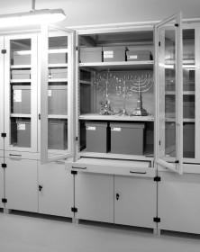 Fotografie mit Ansicht eines geöffneten Glasschranks mit Sicht auf grauen Kartons und drei Leuchter