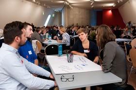 Männer und Frauen sitzen um einen Tisch und diskutieren