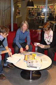 Drei Frauen sitzen um einen Tisch und halten Bücher in den Händen