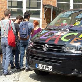 Anna Adam neben ihrem Bus mit internationalen Studenten im Gespräch