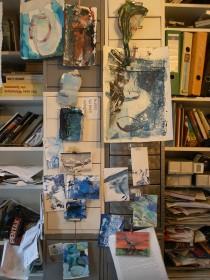 Atelierwand mit Entwürfen und Bücherregalen