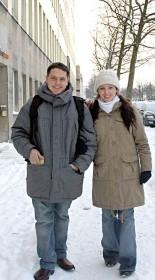 Farbfotografie eines jungen Paares in Winterkleidung auf einer schneebedeckten Straße spazierend