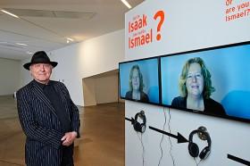 Mann mit Hut vor zwei Bildschirmen, auf denen eine blonde Frau zu sehen ist