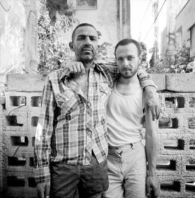 Schwarz-weiß Fotografie von zwei Männern, die Arm in Arm nebeneinander stehen