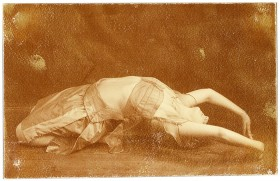 Junge Frau in Tanzpose auf dem Rücken liegend