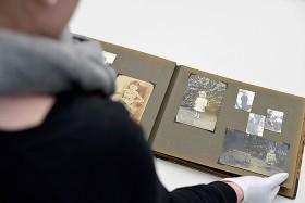 Anna Rosemann betrachtet ein Fotoalbum