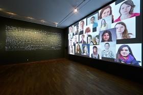 Ausstellungsraum mit Kalligrafie und Multiscreen-Installation