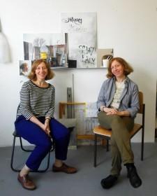 Ein Zwillingspaar auf Stühlen sitzend vor Bildern an der Wand