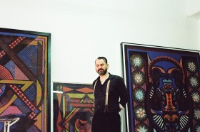 Ein schwarz gekleideter Mann mit Hosenträgern steht zwischen großformatigen Bildern