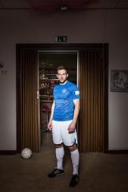 Junger Mann in einem Fußballtrikot vor einer Tür mit Bar und Fußball im Hintergrund