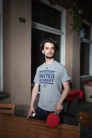 Junger Mann steht mit Tischtennisschläger und Ball an einem Tisch im Freien