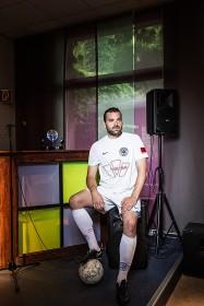 Junger Mann in Sportkleidung mit Fußball vor einer Bar