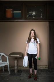 Junge Frau in Sportkleidung mit Handtuch und Trinkflasche