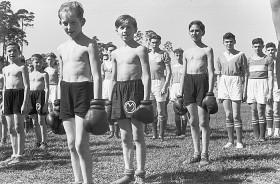 Jungen mit nackten Oberkörpern stehen in Reihen auf einem Sportfeld