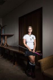 Eine Frau lehnt an einem Tisch und hat einen Hockeyschläger in der Hand