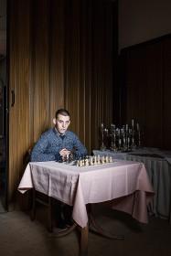 Junger Mann sitzt an einem Tisch mit Schachspiel