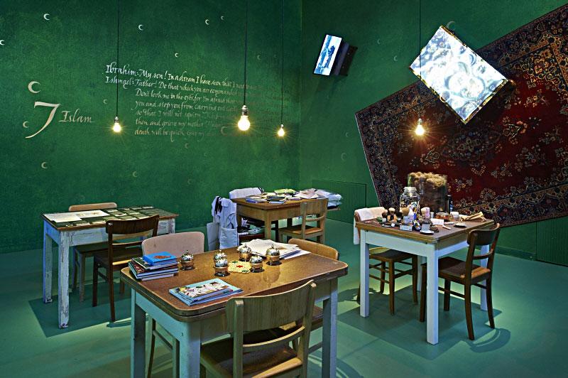 Ein Raum mit Teppich und Bildprojektionen an der Wand, in dem vier Tische stehen, darauf Bücher, drumherum Stühle