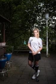 Portrait einer jungen Frau mit einem Hockeyschläger in der Hand