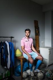 Ein junger Mann sitzt auf einem Tisch in einer Umkleide, unter seinen Füßen liegen Fußbälle