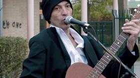 Portrait eines Mannes mit Gitarre am Mikrofon